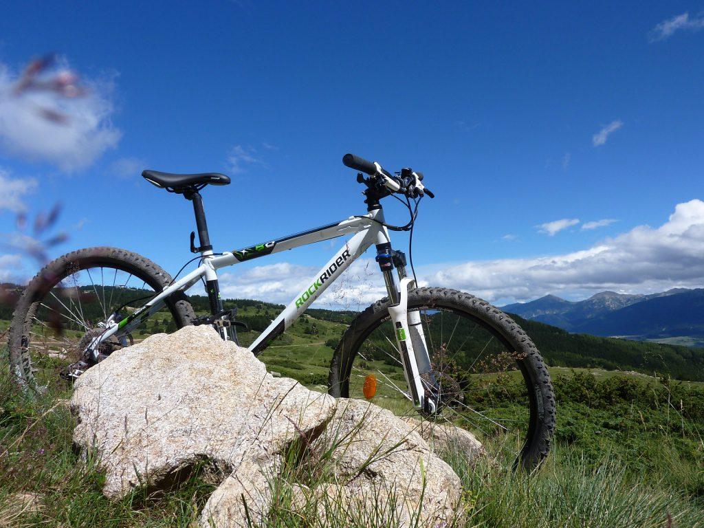 Un vtt posé debout derrière un gros caillou avec la montagne en fond