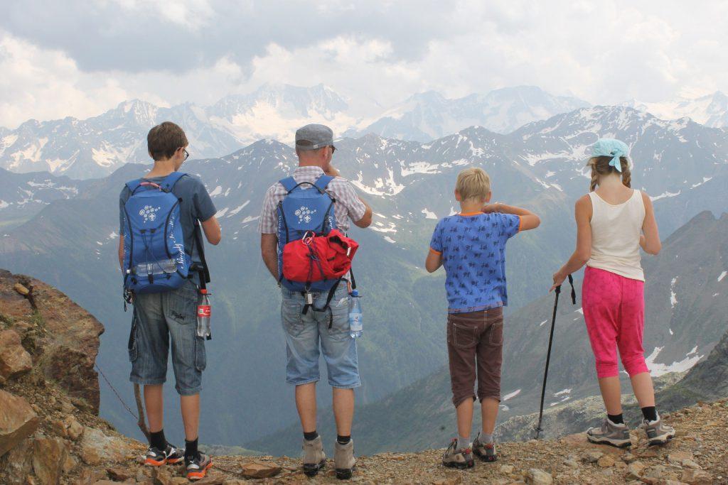 Quatre personnes d'une famille vues de dos en tenues de randonneurs face à une montagne