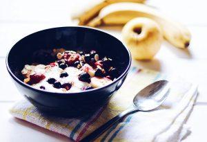 bol de muesli avec yaourt et pomme et bananes posées à côté